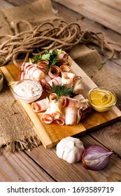 Bacon on a wooden Board, next sauce, onion
