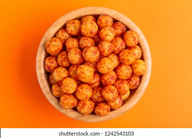 Bacon puff balls in wooden bowl on bright colorful background. Cinema snacks. Copy space
