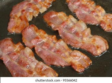 Bacon rashers frying in non-stick pan