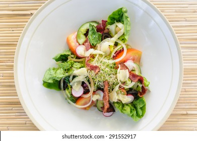 A bacon salad with lettuce, olives, tomatoes, onion, radish and shavings of parmesan cheese.