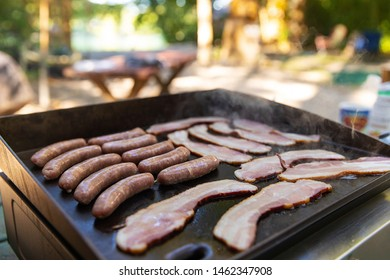 Bacon and sausage cooking on a flat grill outside