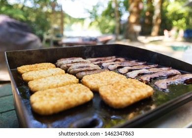 Bacon, sausage and hasbrowns cooking on a grill for breakfast at camp