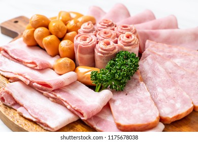bacon, sausage, smoked ham and barbecue bacon on wood board