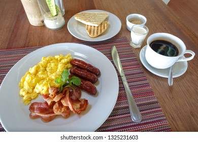 Bacon, Scrambled Eggs, Sausage, and Toast with Coffee - Resort Breakfast