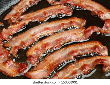 Bacon strips or rashers being cooked in frying pan.