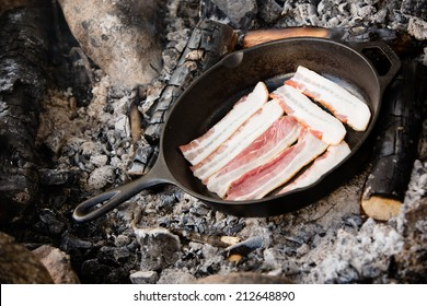 Bacon - This is a shot of bacon being cooked over warm coals from a campfire.
