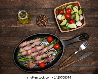 Bacon wrapped asparagus on wooden table.  Cooking asparagus. Food background. Asparagus served on cast-iron frying pan with fresh salad.
