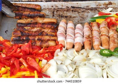 Bacon wrapped hot dogs, onions, jalapenos, and several varieties of bell peppers grilling on an outdoor vendors grill. Close up.