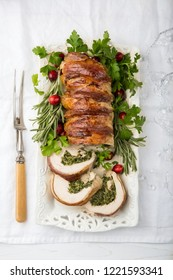 bacon wrapped turkey breast stuffed with spinach and cheese for festive dinner, white background, top view