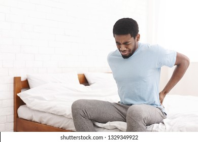 Bad bed. Young african-american guy suffering from back pain in bedroom, waking up in morning, free space
