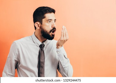 Bad breath. Halitosis concept. Businessman checking his breath with his hand.