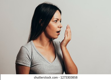 Bad breath. Halitosis concept. Young woman checking his breath with his hand.