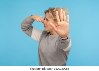 Bad breath. Woman in grey sweatshirt pinching nose with fingers, holding breath to avoid intolerable smell, stinky fart gases, showing stop gesture. indoor studio shot isolated on blue background