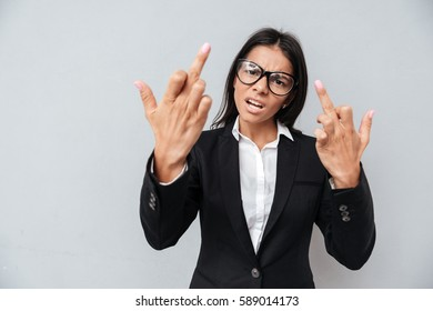 Bad Business woman in suit and eyeglasses which showing middle fingers at camera. Isolated gray background