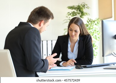 Bad businessman trying to convince to a suspicious client during a difficult negotiation in a desktop at office