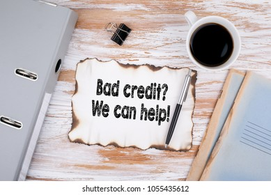 Bad credit, We can help. Business concept. Wooden desk with stationery and a cup of coffee