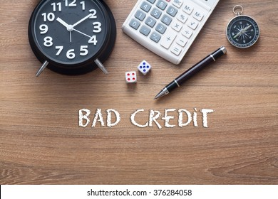 Bad credit written on wooden table with clock,dice,calculator pen and compass