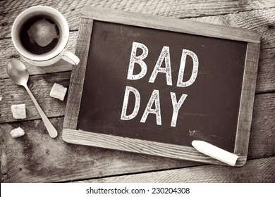 Bad Day sign on Blackboard. Blackboard with Black Friday sign and cup of coffee on wooden background