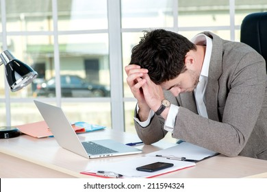 Bad day. tired and depressed businessman sitting in office at the table and working on a laptop while young businessman bowed his head down