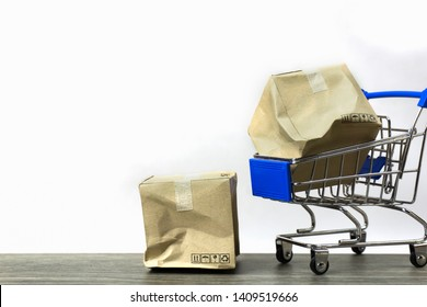 Bad delivery concepts. A damaged container box in small blue shopping cart model and on wood table with white background. Depicts transportation of goods that are inefficient in transportation.