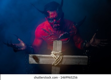 Bad devil or evil spirit guy looks at the cross and open hands that it do not care or fear the god. Devil or ghost standing in the dark of graveyard with foggy. Cross is shining. Devil comes from hell