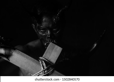 Bad devil or satan holding the holy cross. Bad spirit doesn't afraid the God. It come from hell. He does not afraid sin. Evil spirits get angry, frustrated. The monster looks savage, black and white