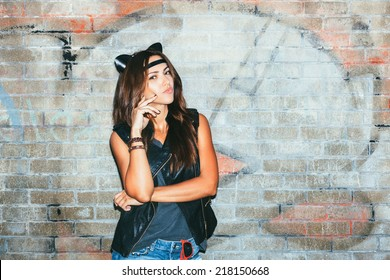 Bad girl  with leather cat ears. Urban scene. Outdoor lifestyle portrait