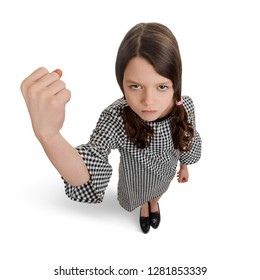 Bad girl showing a big fist and grumpy face. Kid with awful temper and unfriendly attitude.