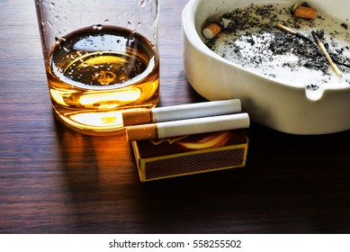 Bad habits. Alcohol and cigarettes are injurious to health. A glass of whiskey, two cigarettes, a match box and an ash tray containing cigarette butts on a wooden table.