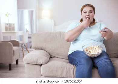 Bad habits. Dreamy red-head woman sitting on the sofa eating popcorn while watching television