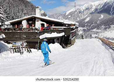 BAD HOFGASTEIN, AUSTRIA - MARCH 9, 2016: People ride by apres ski restaurant in Bad Hofgastein. It is part of Ski Amade, one of largest sking regions in Europe with 760km of runs.
