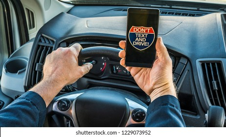 Bad and illegal habit. Close up of the hands of a man driver, holding phone in hand while driving, phone displays no text while driving on screen. Very unsafe driving habit.