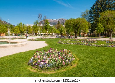 Bad Ischl, Austria - April 20, 2018: People relaxing in a beautiful Kurpark park with colorful blooming flower beds on a sunny spring day.