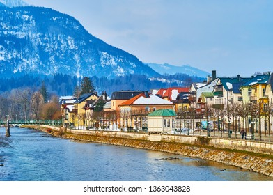 BAD ISCHL, AUSTRIA - FEBRUARY 20, 2019: Esplanade embankment of Traun river with a view on historic quarters, colorful townhouses, souvenir stores and restaurants, on February 20 in Bad Ischl.