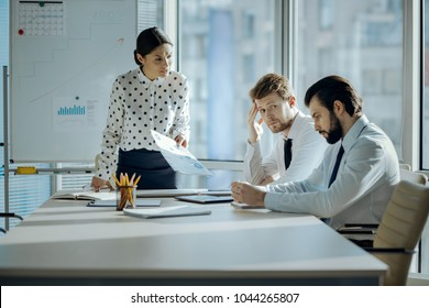 Bad job. Angry female boss having a meeting with her employees and reprimanding them for the poor performance while they looking embarrassed