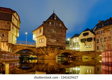 """Bad Kreuznach, Germany - March 02, 2019: famous houses built on the bridge (""""Brückenhäuser"""") across the water """"Mühlenteich"""" illuminated by electric lights during beautiful blue hour at dawn"""