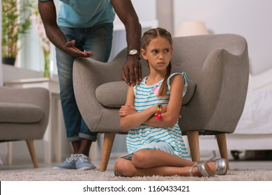Bad mood. Angry upset girl sitting on the floor while having a conflict with her father