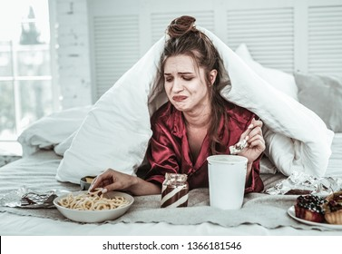Bad mood. Depressed woman seizing stress with lots of sweet