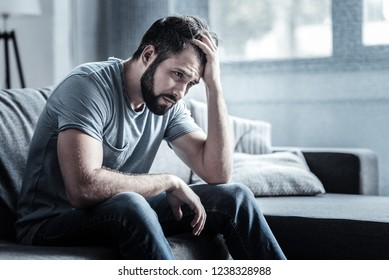 Bad mood. Negative delighted brunette wrinkling his forehead and pressing lips while being deep in thoughts