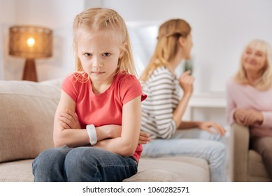 Bad mood. Nice unhappy angry girl turning away from her mother and looking at you while feeling upset