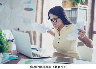 Bad mood. Young angry mulatto businesswoman is casual clothes and glasses is tired from work in the office, crumpling papers and yelling at the laptop