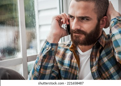 Bad news. Depressed young bearded man expressing negativity while talking on the mobile phone and looking through window