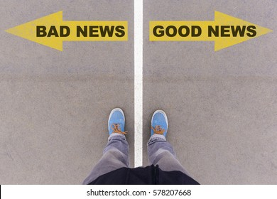 Bad news and good news text on yellow arrows on asphalt ground, feet and shoes on floor, personal perspective footsie concept
