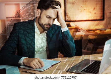 Bad news. Handsome bristled young man in a suit sitting at the table, grabbing his head in despair, having heard disappointing news about his business