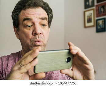 Bad news. Mature man reading sms on smartphone