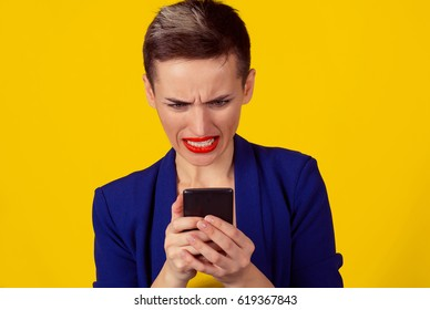 Bad news. Portrait angry mad remorseful young woman looking at mobile phone isolated on yellow background wall. Negative human emotions feelings