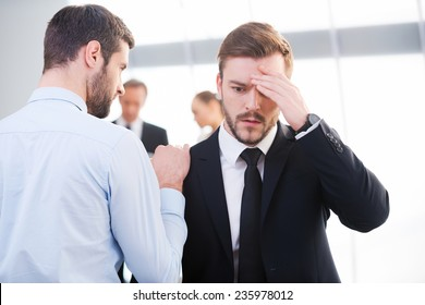 Bad news. Rear view of young businessman consoling his depressed colleague and holding hand on his shoulder with people standing in the background