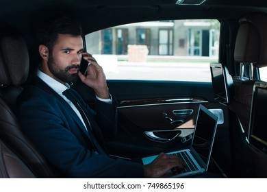 Bad news. Side view of handsome young man using laptop and talking on mobile phone while sitting in car