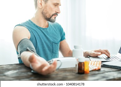 Bad news. Tired upset unshaken man sitting at home in the bright room by the table looking at the laptop and measuring pulse.