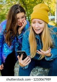 Bad news. Two girlfriends sad girls use a smartphone on the street.